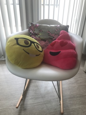 Reversible sequin pillow along with Emoji pillows on display